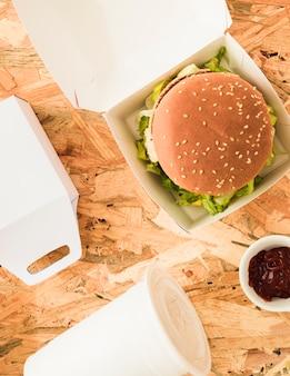 Vista de ángulo alto de una deliciosa hamburguesa con una taza de comida y un paquete de comida