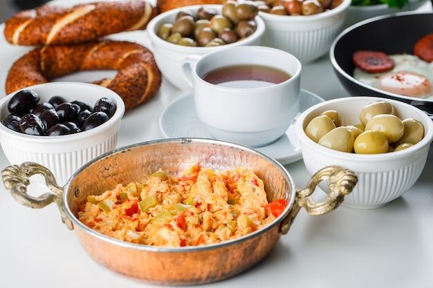 Vista de ángulo alto deliciosas comidas en una olla con una taza de té, panecillos turcos, tomates, verduras en la superficie blanca