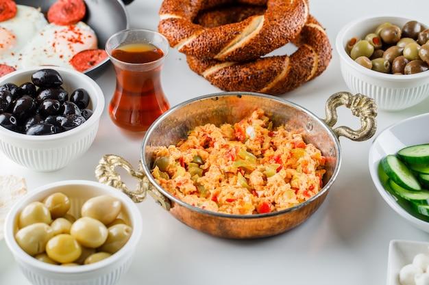 Vista de ángulo alto deliciosas comidas en sartén y olla con ensalada, encurtidos, una taza de té, panecillos turcos sobre superficie blanca
