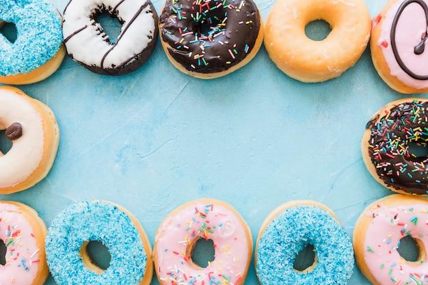 Vista de ángulo alto de donuts frescos coloridos formando marco