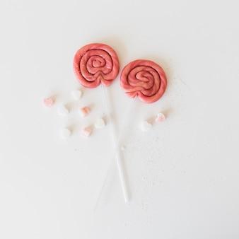 Vista de ángulo alto de dos paletas con caramelos en forma de corazón