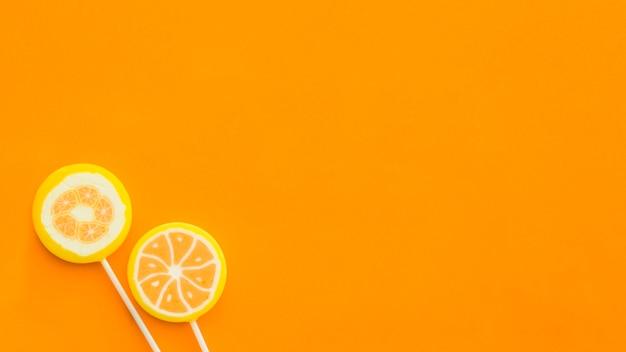 Vista de ángulo alto de dos piruletas en superficie naranja