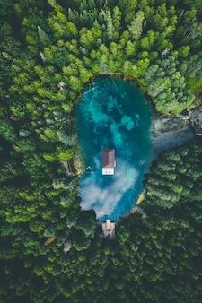 Vista de ángulo alto de un edificio en un lago rodeado de bosques bajo un cielo nublado