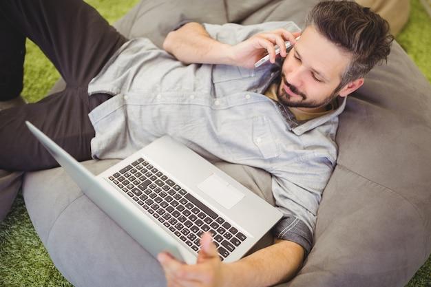 Vista de ángulo alto del empresario usando una computadora portátil y un teléfono móvil en la oficina creativa