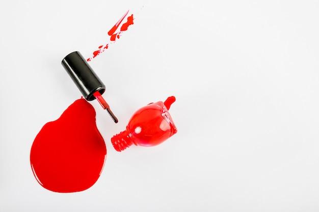 Vista de ángulo alto de esmalte de uñas rojo derramado sobre fondo blanco