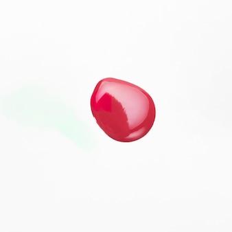 Vista de ángulo alto de esmalte de uñas rojo gota muestra