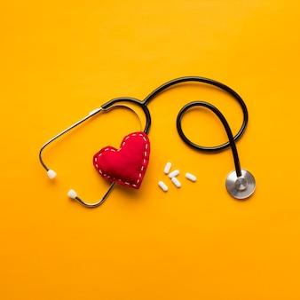 Vista de ángulo alto del estetoscopio; corazón cosido y medicamentos sobre fondo amarillo