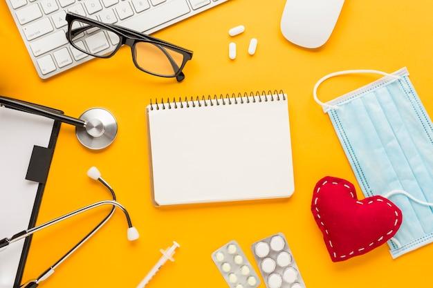 Vista de ángulo alto del estetoscopio; inyección; medicina empacada en blíster; máscara; cuaderno de espiral; cosido en forma de corazón contra el fondo amarillo