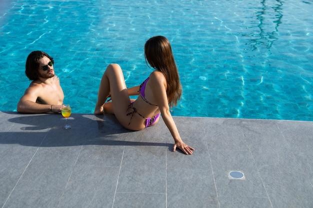 Vista de ángulo alto de la feliz pareja joven junto a la piscina. pareja se relaja en la fiesta de la piscina. concepto de vacaciones de verano
