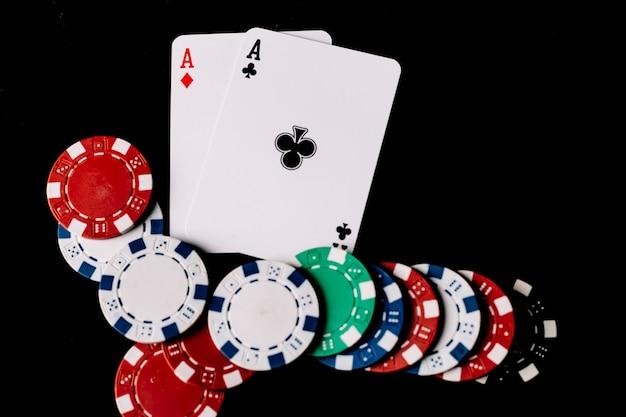 Vista de ángulo alto de fichas de póquer y dos ases jugando cartas sobre fondo negro