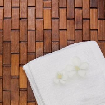 Vista de ángulo alto de flores blancas y toalla en piso de madera