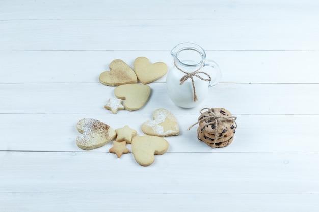 Vista de ángulo alto en forma de corazón y galletas de estrella con jarra de leche sobre fondo de tablero de madera blanca. horizontal