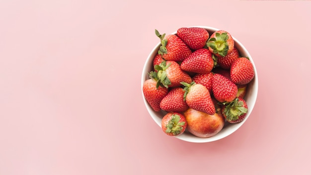 Vista de ángulo alto de fresas frescas y manzanas en un tazón sobre fondo rosa