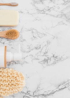 Vista de ángulo alto de guante de matorral; botella cosmética; cepillo y jabón en superficie de mármol.