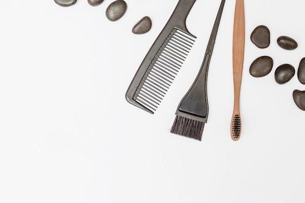 Vista de ángulo alto de haircomb; guijarros y pincel sobre superficie blanca