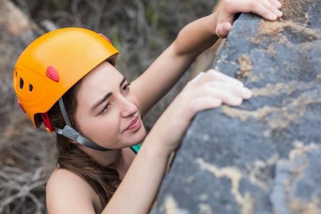 Vista de ángulo alto de hermosa mujer escalando roca