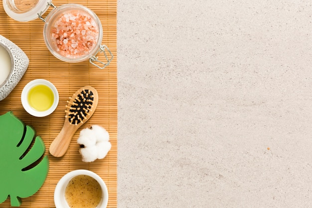 Vista de ángulo alto de un ingrediente de spa y cepillo de pelo en la arena