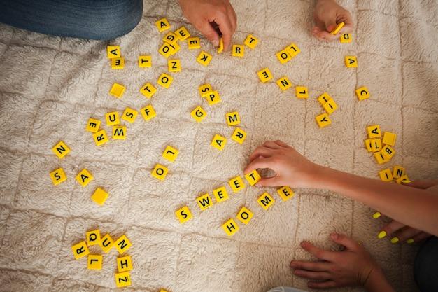 Vista de ángulo alto de juego de scrabble de mano en alfombra
