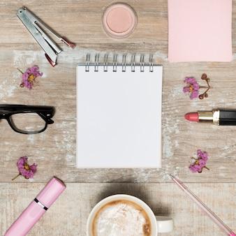 Vista de ángulo alto de la libreta blanca en blanco rodeada de productos cosméticos; taza de café; flores y gafas dispuestas en escritorio de madera.