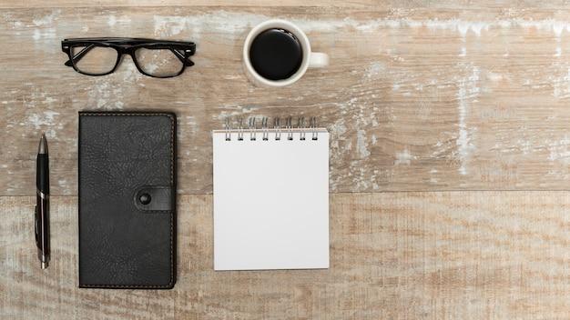 Vista de ángulo alto de la libreta en blanco; diario; bolígrafo; taza de café; anteojos en escritorio de madera