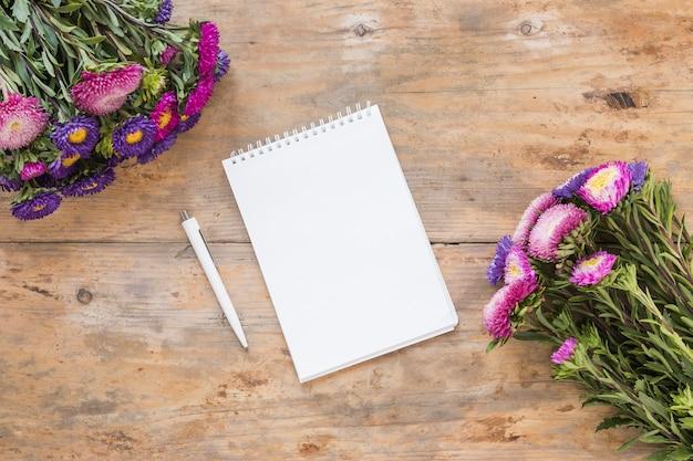 Vista de ángulo alto de la libreta espiral; bolígrafo y ramo de flores en mesa de madera.