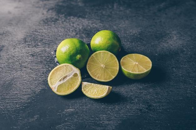 Vista de ángulo alto limones verdes con rodajas sobre fondo negro con textura. horizontal