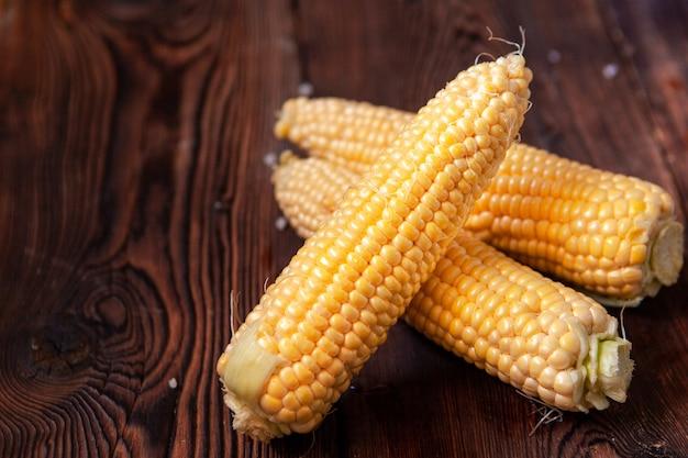 Vista de ángulo alto de maíz fresco en una mesa de madera oscura