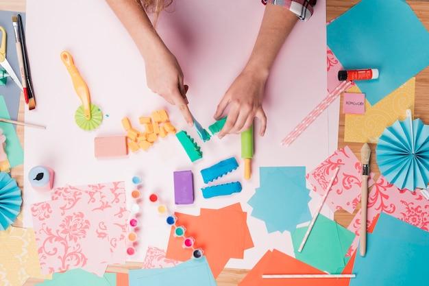 Vista de ángulo alto de la mano femenina preparando arte de arcilla en la mesa