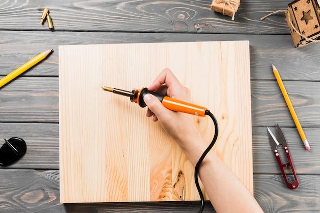 Vista de ángulo alto de la mano que sujeta la máquina de soldar en el tablero de madera para cortar la forma