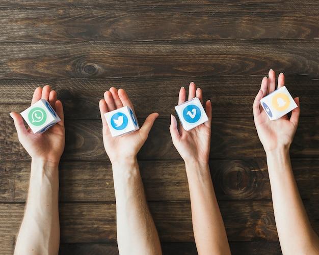 Vista de ángulo alto de manos sosteniendo cajas de iconos de aplicaciones móviles vivos