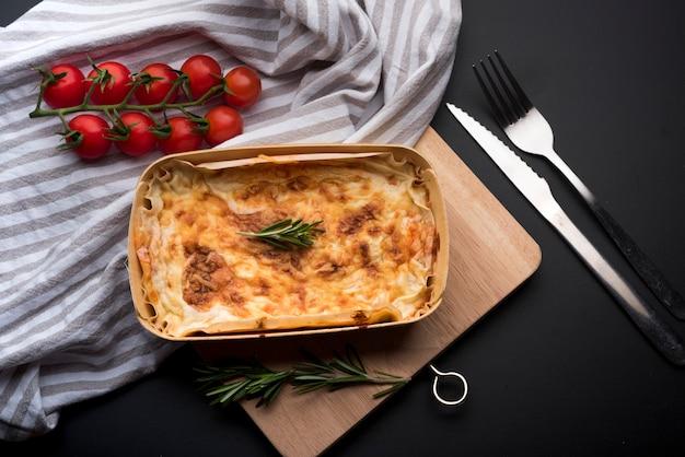 Vista de ángulo alto de mantel; ingrediente fresco y deliciosa lasaña