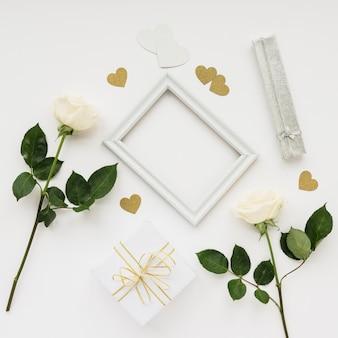 Vista de ángulo alto del marco de imagen; rosas; pegatinas en forma de corazón y regalo en superficie blanca.