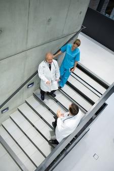 Vista de ángulo alto de médicos y cirujanos que interactúan entre sí en la escalera