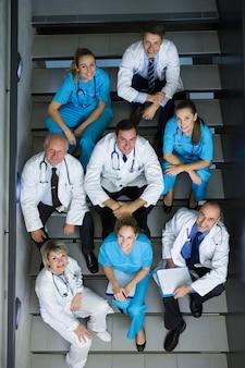 Vista de ángulo alto de médicos y cirujanos sentados en la escalera