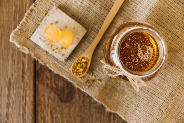 Vista de ángulo alto de la miel; semillas de polen de abeja y caramelos en tela de saco