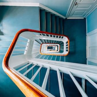 Vista de ángulo alto de una moderna escalera de caracol en una exposición bajo las luces