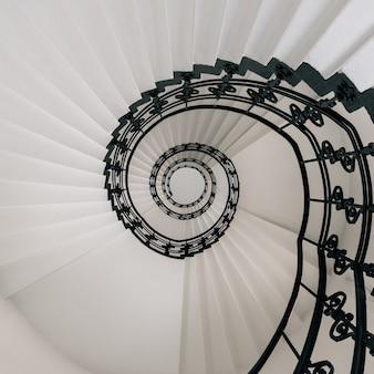 Vista de ángulo alto de una moderna escalera de caracol bajo las luces