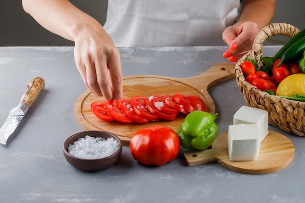 Vista de ángulo alto mujer agregando sal en rodajas de tomate en la tabla de cortar con cuchillo, queso, pimiento verde, sal en la superficie gris