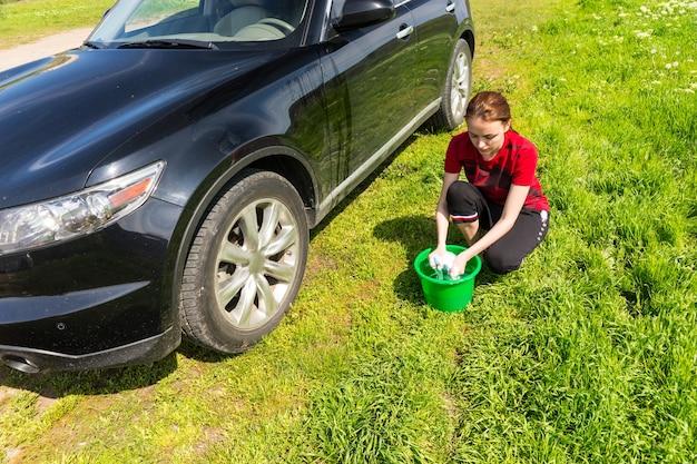 Vista de ángulo alto de mujer con cubo verde escurriendo esponja jabonosa y lavado de vehículo de lujo negro en campo verde en día soleado con cielo azul