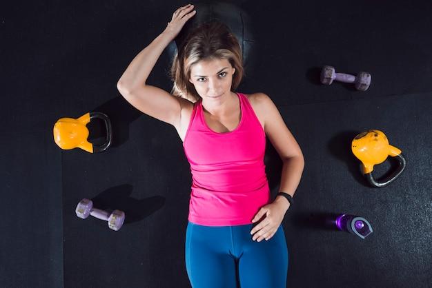 Vista de ángulo alto de la mujer en forma relajante en el piso cerca de equipos de ejercicio