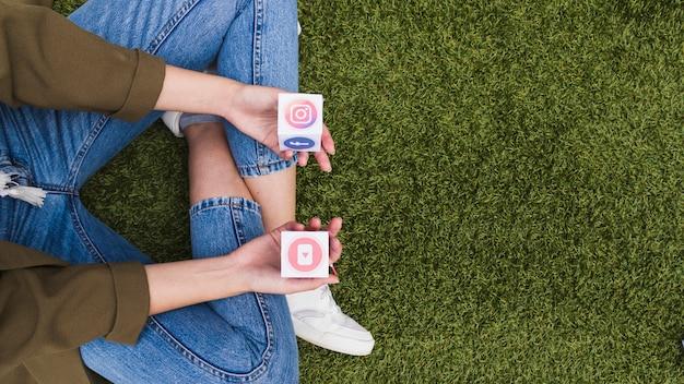 Vista de ángulo alto de una mujer con iconos de aplicaciones móviles de medios sociales en la mano