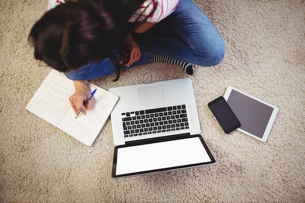 Vista de ángulo alto de mujer con laptop en alfombra