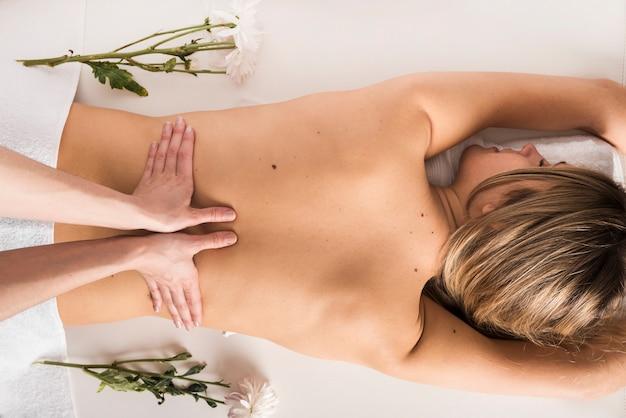 Vista de ángulo alto de una mujer que recibe masaje de espalda de terapeuta