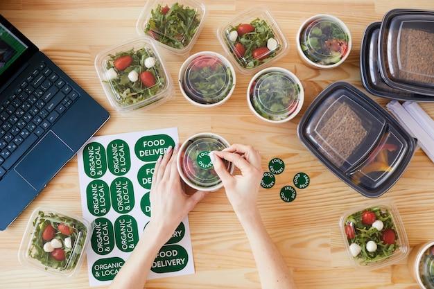 Vista de ángulo alto de mujer sentada en la mesa de madera que hace entrega de alimentos saludables en la oficina