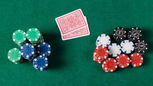 Vista de ángulo alto de naipes y fichas en la mesa de póker verde