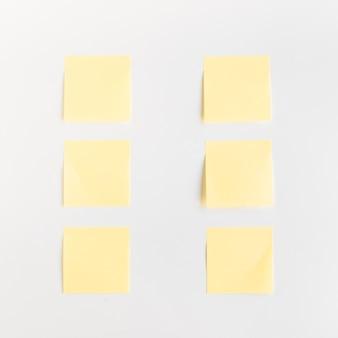 Vista de ángulo alto de notas adhesivas amarillas dispuestas en una fila en el fondo blanco