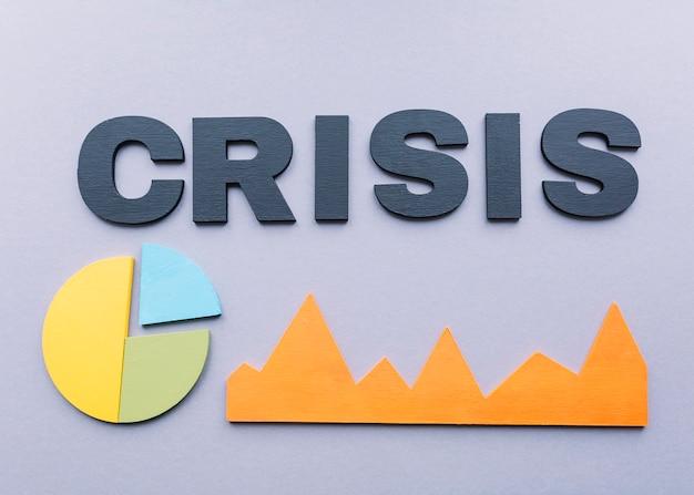 Vista de ángulo alto de la palabra crisis con gráficos sobre fondo gris