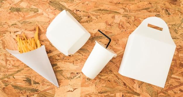 Vista de ángulo alto de papas fritas; disposición de vasos y envases en superficie de madera.