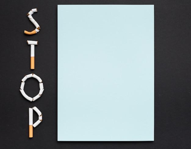 Vista de ángulo alto de papel en blanco con texto de parada hecho de cigarrillos