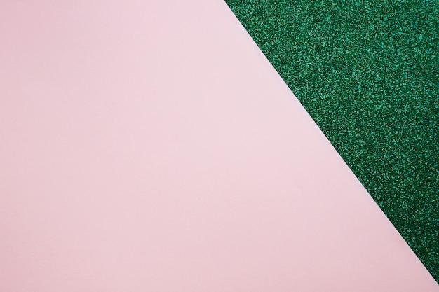 Vista de ángulo alto de papel de cartón rosa en alfombra verde